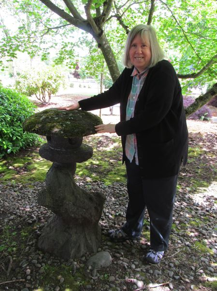 by: PHOTO BY ELLEN SPITALERI - Elise Lunas, chairwoman of the Oregon City Sister City Committee, poses with a stone lantern in the Peace Garden.