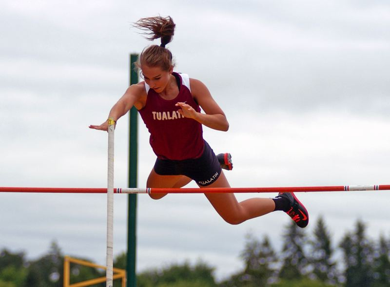 by: DAN BROOD - Tualatin High School senior Laura Taylor soars over the bar during Friday's girls pole vault competition at the Class 6A state track and field championships held at Hayward Field in Eugene.