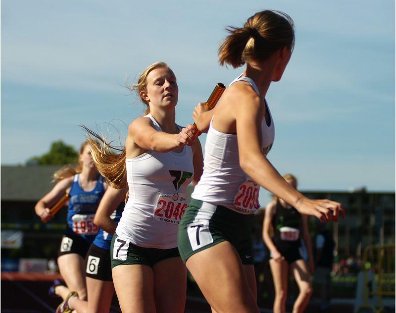 by: DAN BROOD - Tigard junior Kaylie Boschma (left) hands the baton to senior Lindsey Rosette during the Class 6A girls 4 x 400-meter relay event.