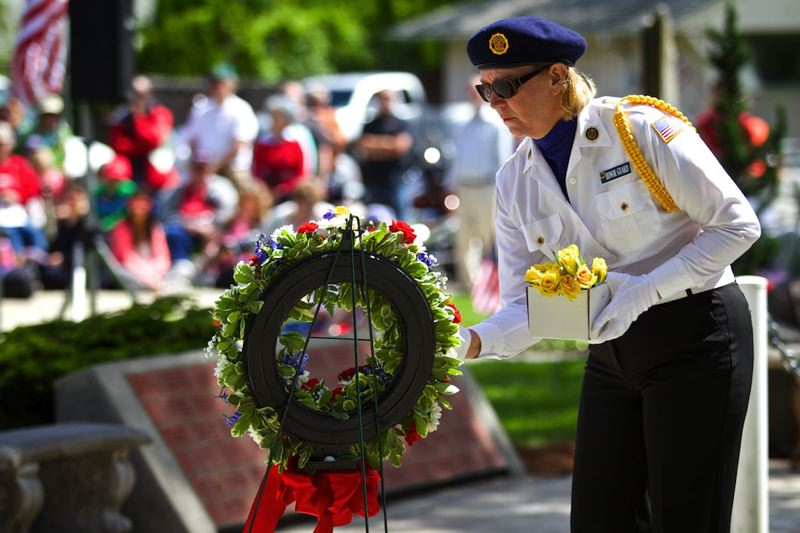 by: TIMES PHOTO: JAIME VALDEZ - Christine Murray, a member of the Beaverton American Legion Post 124's Honor Guard, places yellow roses on a memorial wreath in recognition of local veterans who recently died.
