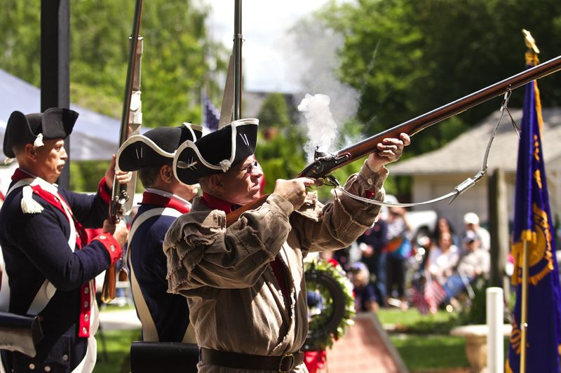 by: TIMES PHOTO: JAIME VALDEZ - Members of The Sons of the American Revolution Musket Team fire rifle volleys near the end of the Memorial Day Program at Beaverton Veterans Memorial Park.