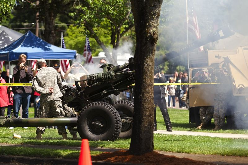 by: TIMES PHOTO: JAIME VALDEZ - Members of Governor's Own Bravo Battery 2-218th Field Artillery fire volleys from a Howitzer near the end of the Memorial Day Program at Beaverton Veterans Memorial Park. The blank rounds contained 1.7 pounds of black powder giving off three loud bangs and a lot of smoke.