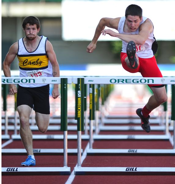 by: JOHN LARIVIERE - Clackamas senior Connor McLean (right) is well in front of Canby senior Timothy Johnson as McLean heads for first place and a school record in the 110-meter high hurdles at the 2014 Class 6A High School Championship Track and Field Meet.