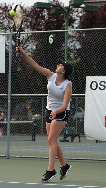 by: JOHN WILLIAM HOWARD - Lexi Normine serves late in the first set of the first round of doubles action on Thursday, May 22. The St. Helens doubles team took third place at the OSAA 5A State Championships.