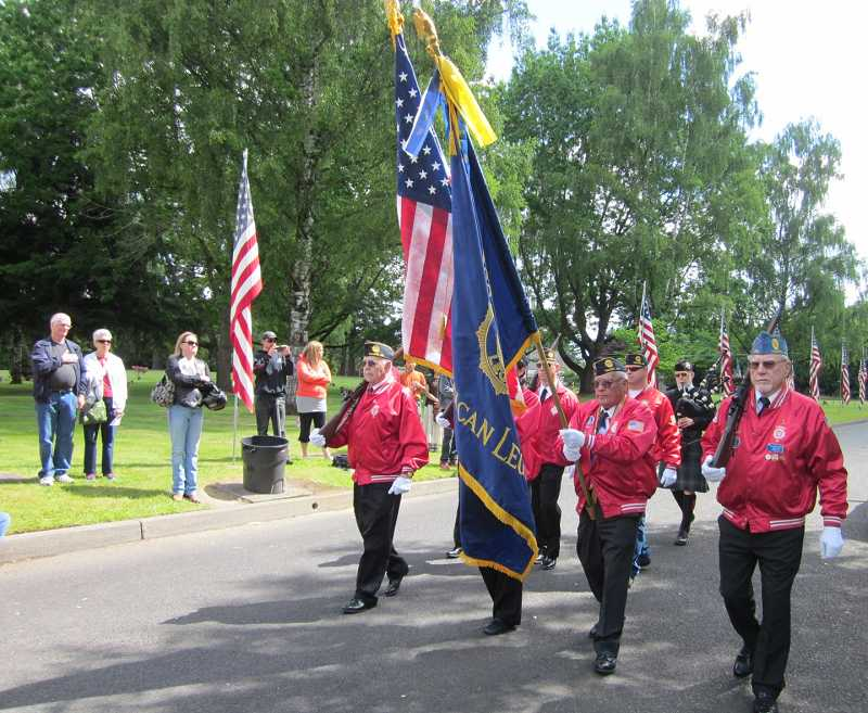 by: TIMES PHOTO: BARBARA SHERMAN - The Tigard American Legion Post 158 color guard marches along the road in Crescent Grove Cemetery to post the colors at the beginning of the Memorial Day ceremony that the legion traditionally hosts.