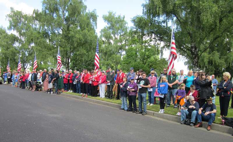 by: TIMES PHOTO: BARBARA SHERMAN - A crowd made up of American Legion members and regular citizens of all ages watches as the Post 158 color guard marches in with the U.S. and Oregon flags to post the colors.