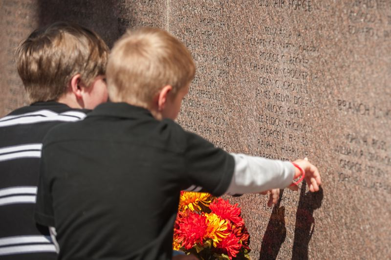 by: SPOKESMAN PHOTO: JOSH KULLA - Children look for familiar names at Wilsonville's Korean War Memorial.