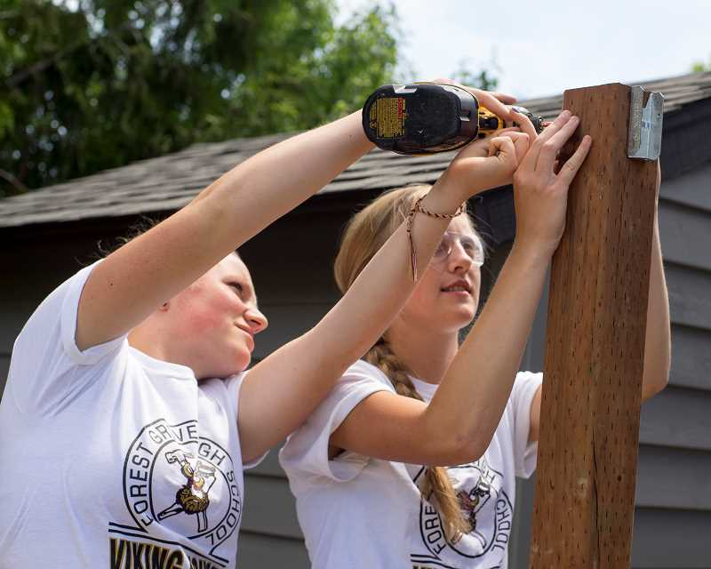 Charlotte Sidman (left) and Tess Sivak attach brackets to posts at Viking House. Crew member Cody Fellows used to tease them, saying Its painful to watch you guys swing a hammer, Sivak said. Sometimes that made him tough to work with, she said, but when he died, we just cried for like, days.