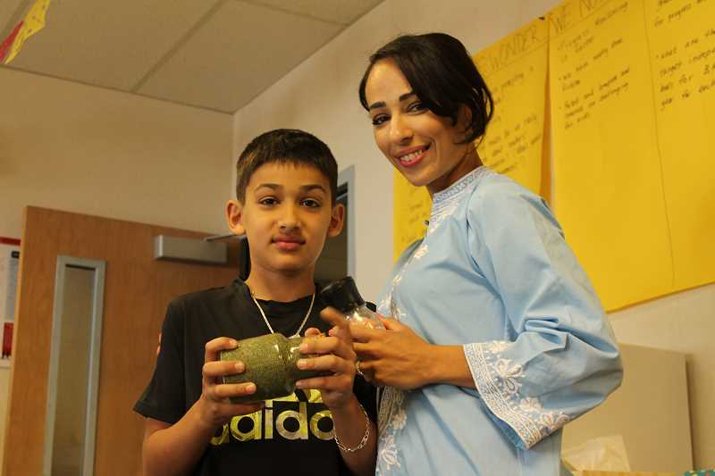 by: SPOKESMAN PHOTO: KATE HOOTS - Lida Ajami and her fourth-grade son Suhai shared some highlights of Lebanese cuisine with the Boeckman Creek Community May 16. The cooking demonstration is part of a series organized by ELL teacher Jane McGraw.