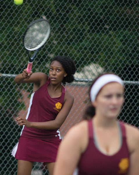 by: NEWS-TIMES PHOTO: CHASE ALLGOOD - Forest Grove's Karimi Nyamu hits a serve during last weekend's state tournament while doubles teammate Natalie Brandt waits at the net.
