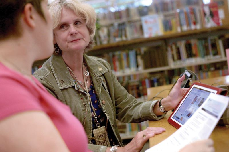 by: TRIBUNE PHOTO: JONATHAN HOUSE - Holgate Library branch Administrator Victoria Oglesbee works with an iPad at the Multnomah County libary branch. The library offers computer classes geared toward increasing digital literacy.