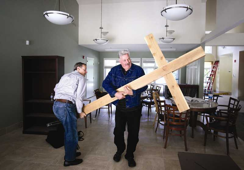 by: TIMES PHOTO: JONATHAN HOUSE - Portland Community Church Lead Pastor Ron Kincaid, left, helps Dennis Woodruff move a large cross into the church sanctuary in its new building at 7100 S.W. Scholls Ferry Road.