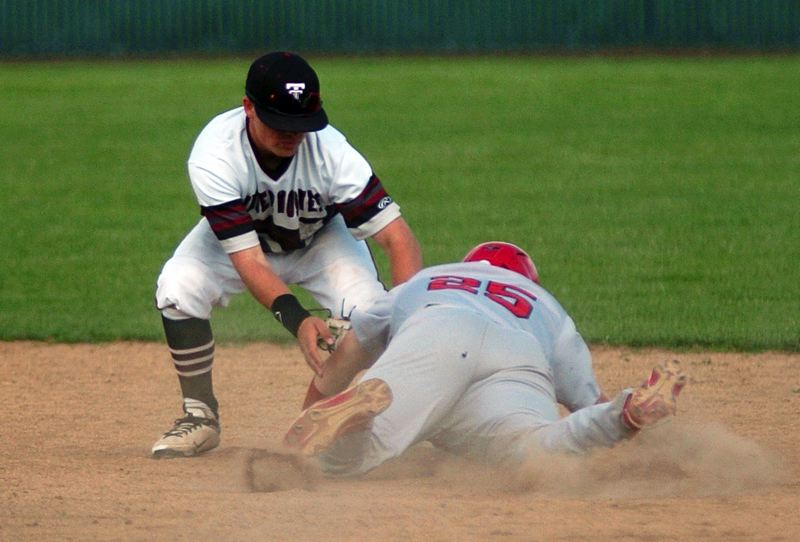by: DAN BROOD - OUTTA THERE -- Tualatin junior shortstop Tanner Marsh (left) tags out David Douglas' Tyler Kinne on a stolen base attempt in Monday's game.