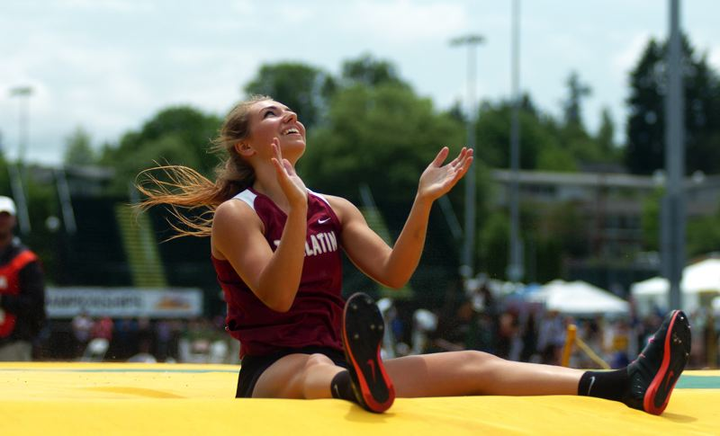 by: DAN BROOD - I DID IT -- Tualatin senior Laura Taylor smiles and claps her hands after clearing a new meet-record height of 12-8 in the pole vault competition at the Class 6A state track and field championships.