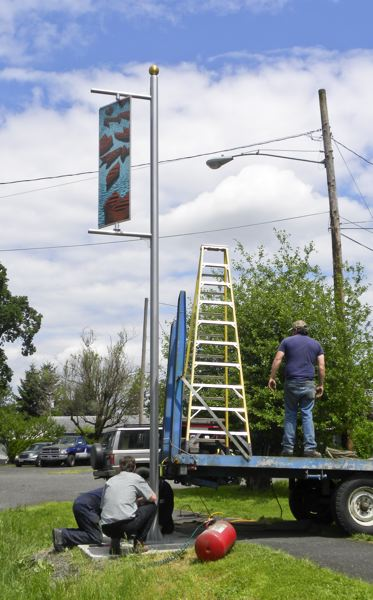 by: COURTESY OF THE CITY OF ST. HELENS - A work crew anchors the new steel pole that holds up an art banner at Old Portland Road and South 11th Street in St. Helens into place Friday, May 16.
