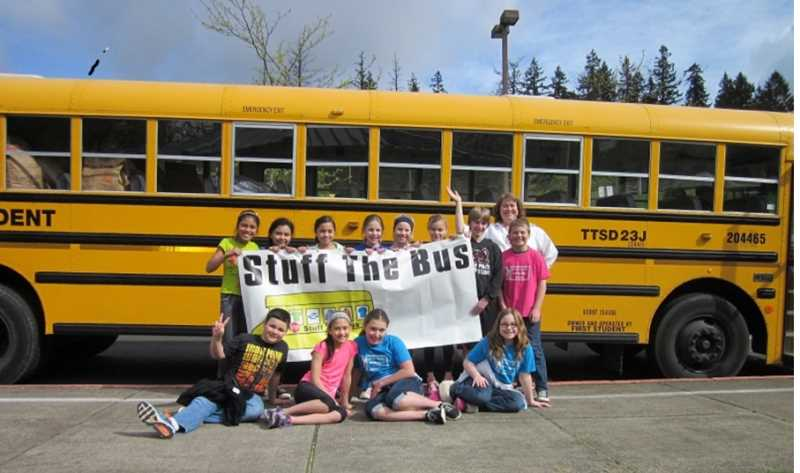 by: BARBARA SHERMAN - SELFLESS GIVING - Deer Creek Elementary School counselor Dianne Wilson poses with some leadership students in front of the bus after all the PJs have been loaded.