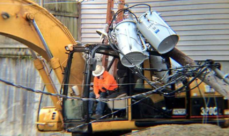 by: KOIN 6 - Two men doing road work on Southwest Main Street were briefly trapped inside their excavator on Monday after a power pole crashed into it.