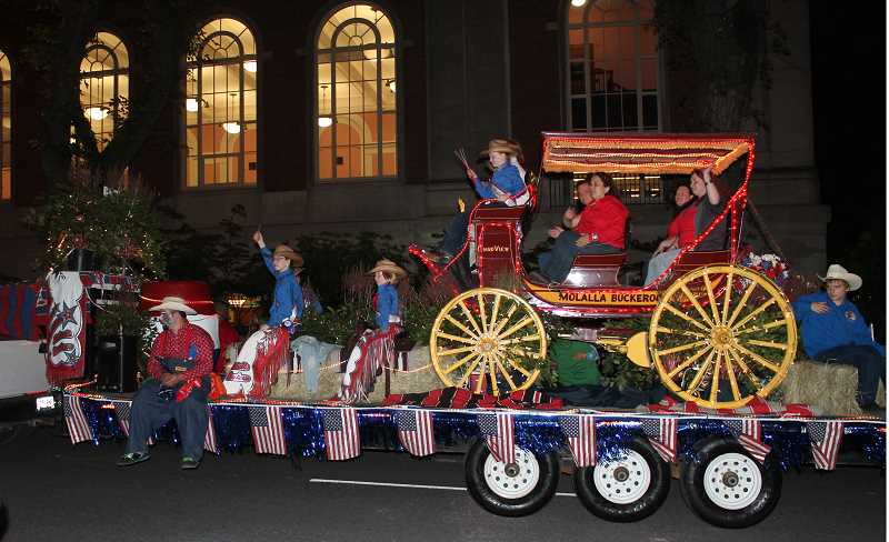 by: JIM BESEDA - The Molalla Buckeroo float passes the Multnomah County Library in downtown Portland during the Starlight Parade.