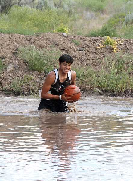 by: JEFF WILSON/THE PIONEER - Miklo Hernandez wades through the mud during Saturday's Challenge portion of the Wild Canyon Games.