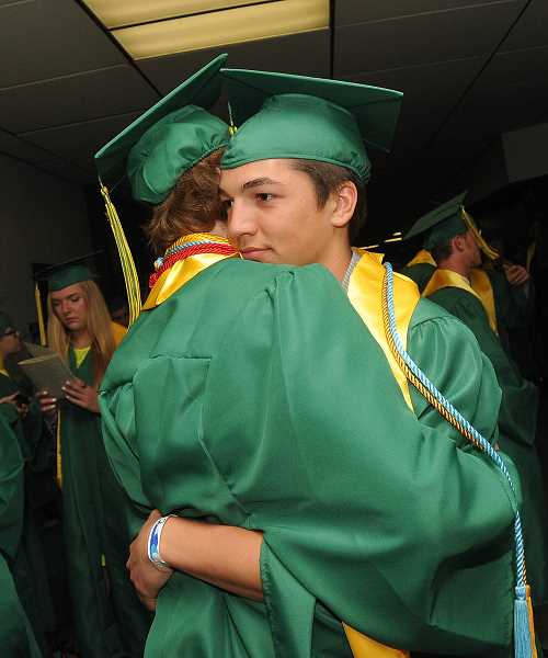 by: TIDINGS PHOTO: VERN UYETAKE - Karter Ferrin gives a big hug to Kenny Whitbey shortly before the start of the commencement ceremony.