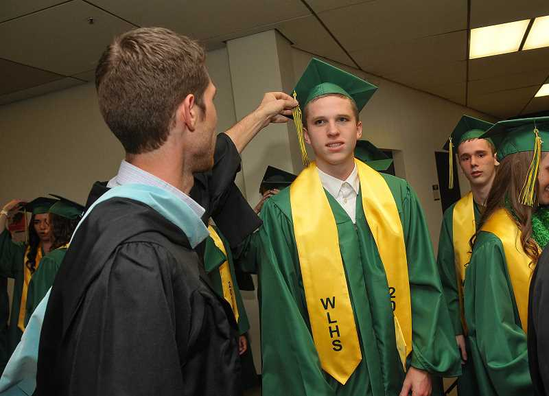 by: TIDINGS PHOTO: VERN UYETAKE - WLHS civics instructor Brian Kuzma helps Hayden Coppedge straighten his tassel.