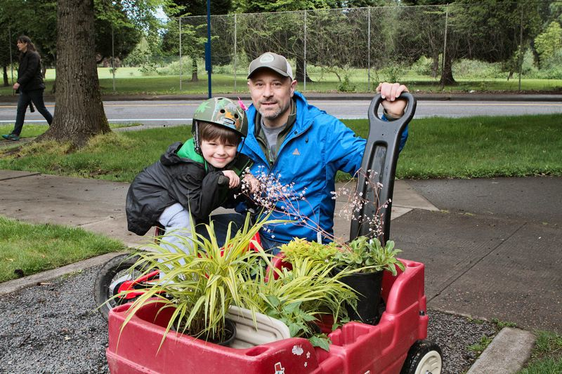 by: DAVID F. ASHTON - Davis Joy and his dad, Brad, get a red-wagon-full of plants at the Eastmoreland Gardens annual plant sale in May.