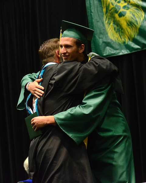 by: TIDINGS PHOTO: VERN UYETAKE - Nathan Blanchard give Principal Lou Bailey a big hug after receiving his diploma.