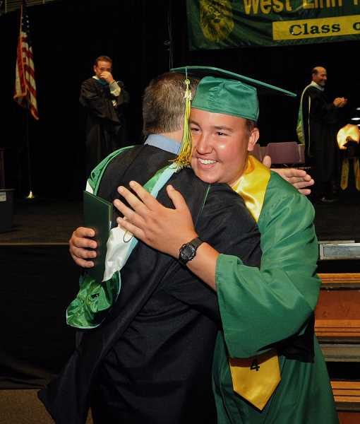 by: TIDINGS PHOTO: VERN UYETAKE - Jacob Stoneking hugs instructor Greg Brean after receiving his diploma - and a standing ovation.