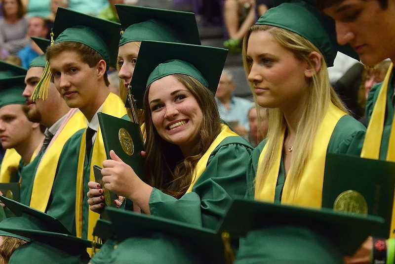 by: TIDINGS PHOTO: VERN UYETAKE - Devyn Pratt beams as she shows off her diploma.