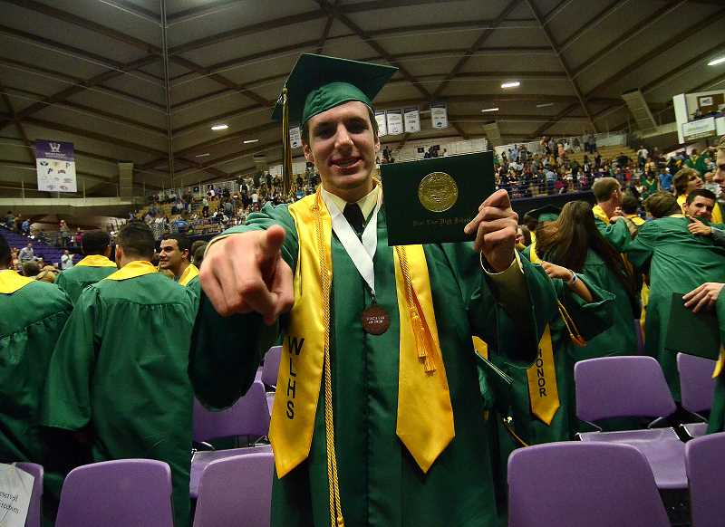 by: TIDINGS PHOTO: VERN UYETAKE - Kevin Edwards proudly shows off his diploma.