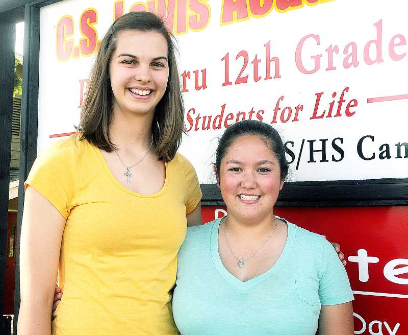 by: SETH GORDON - The long haul - C.S. Lewis Academy Mikaela Raudsepp (left) and Halah Grobey began their careers at the Christian school as preschoolers and finished them Saturday as valedictorian and salutatorian, respectively.
