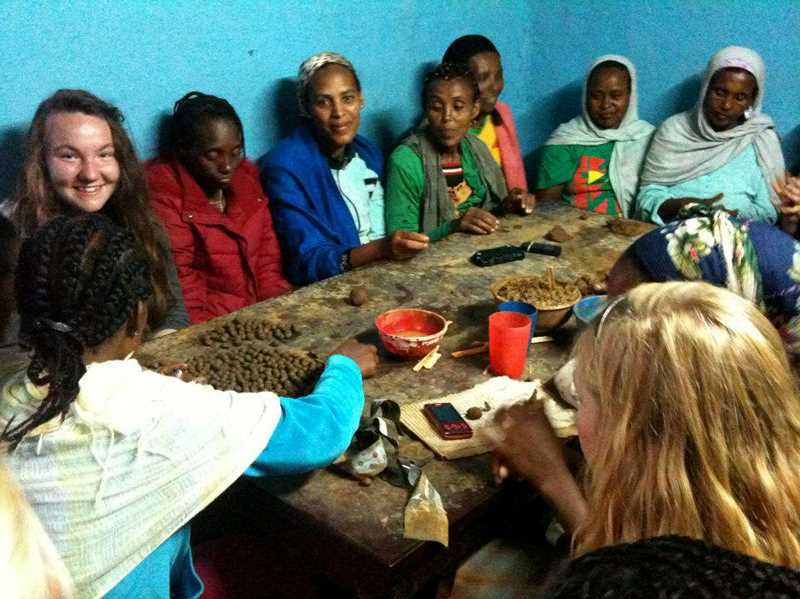 by: COURTESY PHOTO - Sunny Sidman (left) learns how to make clay beads from Ethiopian women who create and sell them. Sidman met the women while building a cafeteria for local school children in Ethiopia during her trip in 2012.