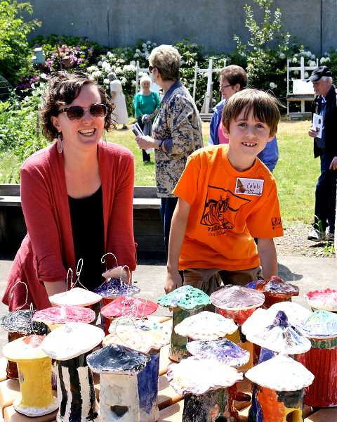 by: COURTESY PHOTO: JIM AND DIANE MORRIS - Teresa Perrin, of the Forest Grove Community School, and first-grader Caleb Beaulieu, display birdhouses hand-crafted by first- and second-graders in the Backyard Garden behind the Old Train Station, an area stewarded by the community school.