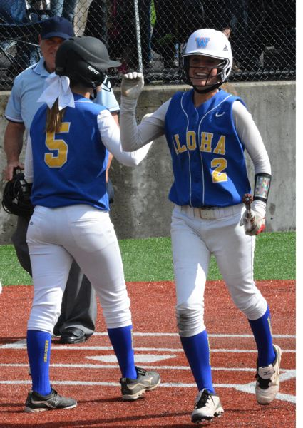 by: TIMES PHOTO: MATT SINGLEDECKER - Aloha third baseman Shelby Ratcliffe celebrates the Warriors first run of the game with Ali Locke in the bottom of the second inning against Glencoe.
