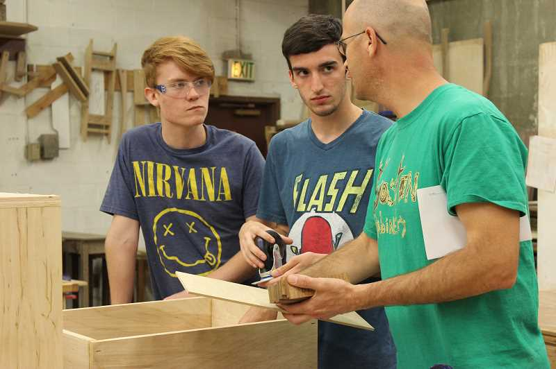 by: NEWS-TIMES PHOTO: KATE STRINGER - Gaston Woods 3 students Cody Jeffries (left) and Nate Lewis (right) listen to teacher Wade Sims explain how to attach wheels to plywood. The wheels will make the judges bench maneuverable for easy BOLI courtroom set-up.