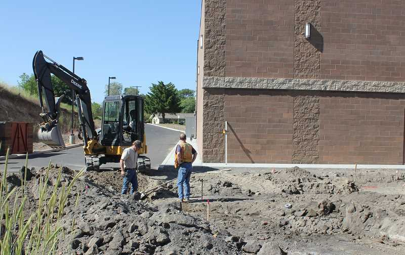 by: SUSAN MATHENY - Scott Goodrich, left, works on preparing the ground adjacent to Madras Cinema 5 for construction of a dialysis clinic, which he expects to be completed next spring.