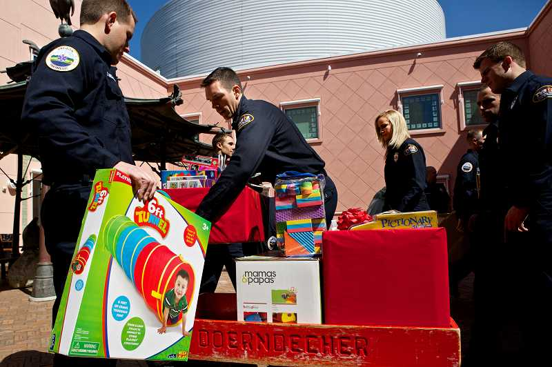 by: TIMES PHOTO: JAIME VALDEZ - Thirteen Tualatin Valley Fire & Rescue firefighter recruits load up a collection of toys to deliver Friday to Oregon Health and Science University's Doernbecher Children's Hospital.