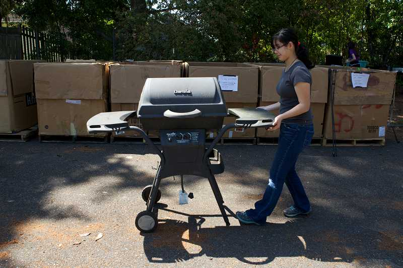 by: TIMES PHOTO: JAIME VADLEZ - Selina Teng, 14, pushes a donated barbecue to be recycled during an event for Rachel Carson Environmental School at Five Oaks Middle School. Teng is a eighth-grader at Summa North, which is an advanced program at Meadow Park Middle School.