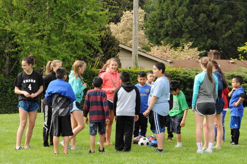 by: COURTESY PHOTO: BRETT COLLINS - Sydney Collins, center, coaches students at a soccer camp she coordinated in May at Vose Elementary School.