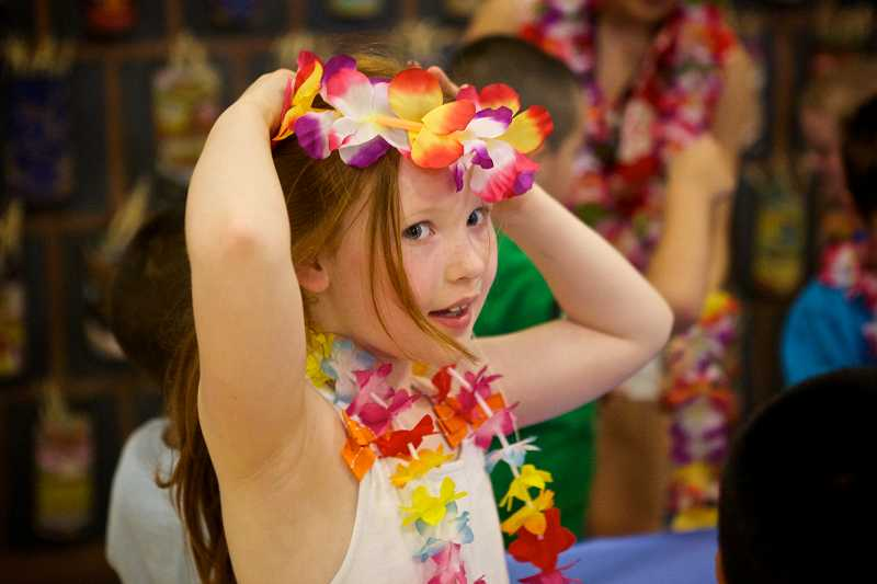 by: TIMES PHOTO: JAIME VALDEZ - First-grader Sydney Randall tries on a lei headband during Beaverton Education Foundation's Culture Week at McKay Elementary School on Friday afternoon.