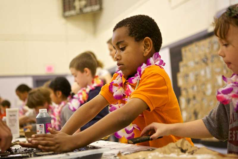 by: TIMES PHOTO: JAIME VALDEZ - First-grader Kerod Dugo makes a Tapa cloth on a brown paper bag during Beaverton Education Foundation's Culture Week at McKay Elementary School.