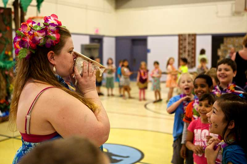 by: TIMES PHOTO: JAIME VALDEZ - Valerie Griffiths, co-coordinator Culture Week at McKay Elementary School, blows a seashell horn to entertain first-graders at the school.