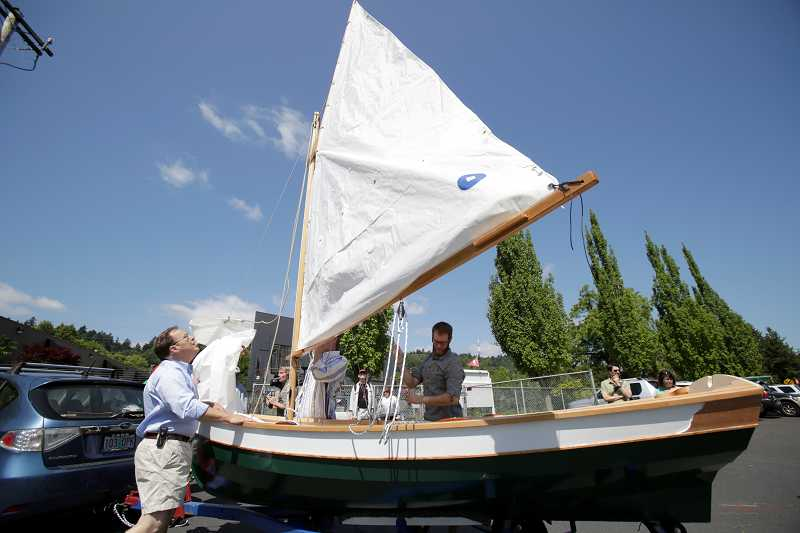 by: TIMES PHOTO: JONATHAN HOUSE - Peter Crim of the Willamette Sailing Club inspects The Sparrow, a boat built by students of Merlo Station Community High School.
