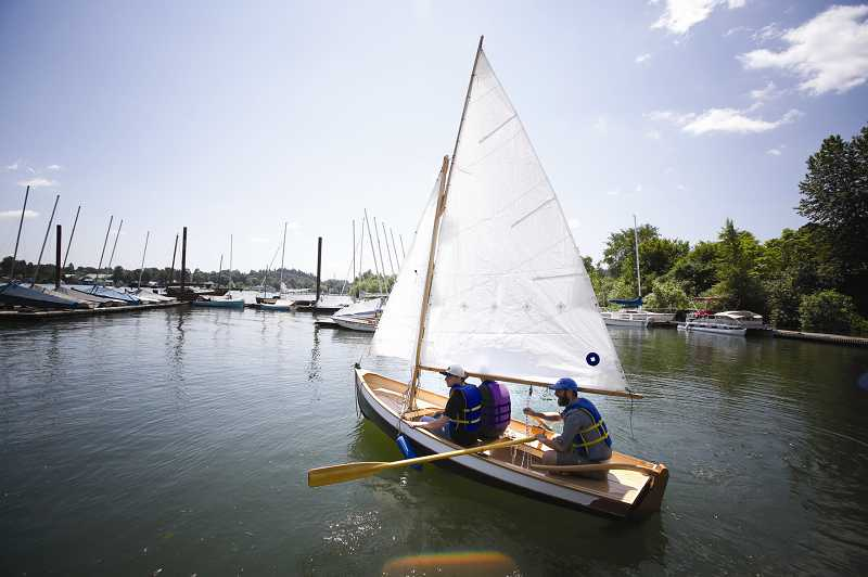 by: TIMES PHOTO: JONATHAN HOUSE - Merlo Station High School students Chris Luethe and Stephen Birtchet, along with sailing instructor Bill Wessinger, take out the boat students built as part of a science, math and engineering project.