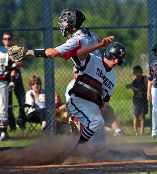 by: DAN BROOD - ANOTHER RUN -- Tualatin junior Trevor Riese slides in for a run during the Wolves' state playoff quarterfinal win over McMinnville.