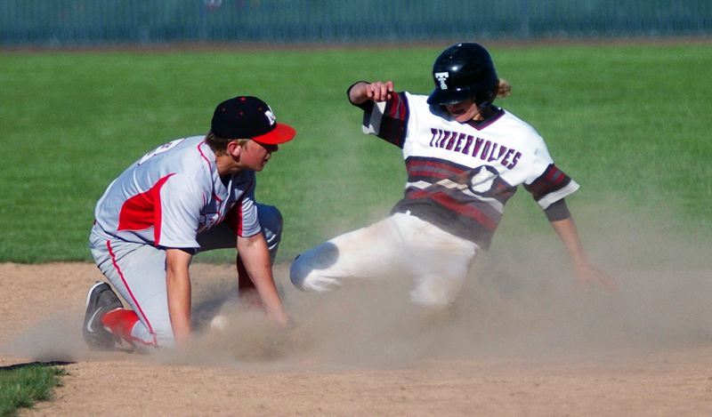 by: DAN BROOD - TAKE A BASE -- Tualatin sophomore Chase Anderson (right) steals second base in the Wolves' win over McMinnville.