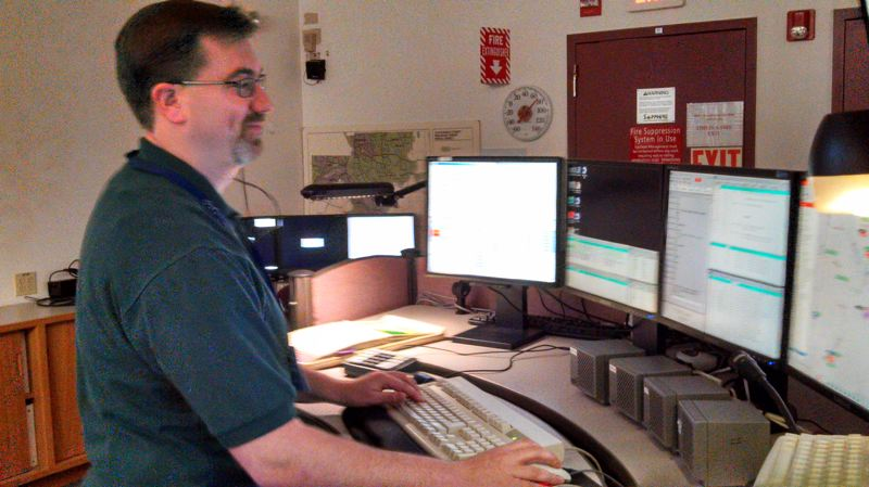 by: SUBMITTED PHOTO - C-COM lead dispatcher Kory Oman usually feels right at home in front of four computer screens and four radios to help coordinate police and fire units in Clackamas County.