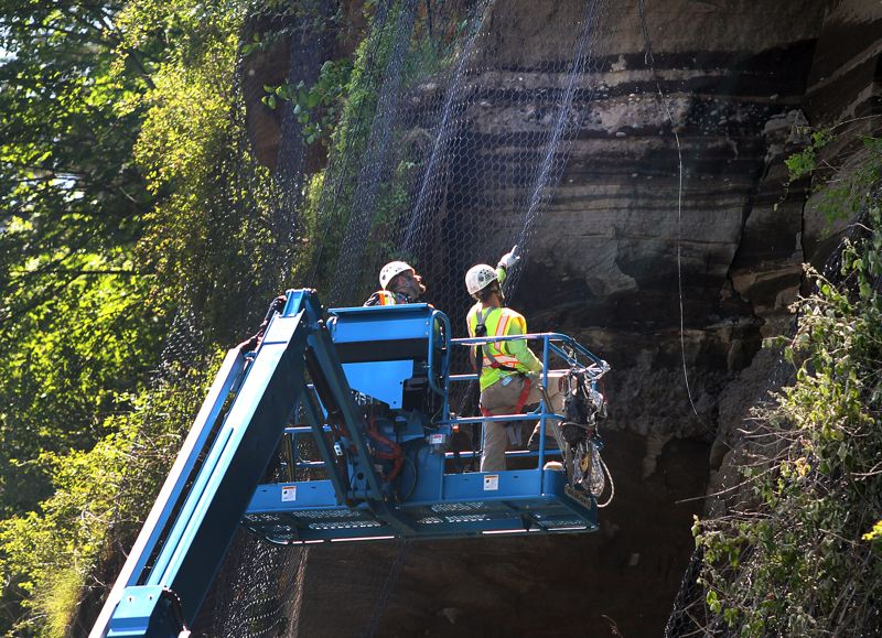 by: OUTLOOK PHOTO: CARI HACHMANN - Rock specialists scoping the 120-foot hillside in Troutdale.