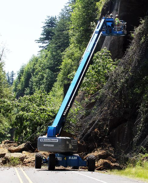 by: OUTLOOK PHOTO: CARI HACHMANN - Crews used a lift Friday, June 6, to check the hillside for loose rock. Work continued Saturday, but clean up efforts will be halted until ODOT can bring in additional equipment, officials say.