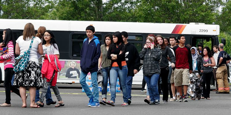 by: OUTLOOK PHOTO: JIM CLARK - The first bus load of students from Reynolds High School arrive at the Wood Village Town Center where they reunited with parents.